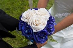 Photo rapprochée du bouquet de la mariée entre les mains des nouveaux mariés