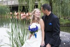 Le marié et la mariée assis devant un étang ou l'on peut voir des flammands roses en arrière plant