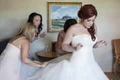 La mariée en préparation avec ses demoiselles d'honneurs l'aidant à vêtir sa robe