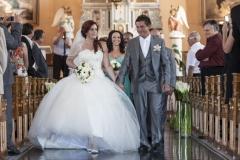 Le marié et la mariée descendant l'allée pour sortir de l'église