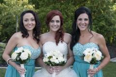 La mariée et ses deux demoiselles d'honneurs tenant chaqu'un leur bouquet, prennent la pose.