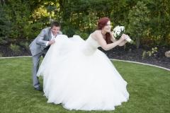 Le marié regardant sous la robe de la mariée d'un air taquin