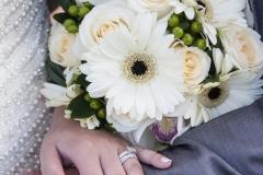 Photo rapprochée du bouquet et des anneaux de mariages portés par le marié et la mariée.