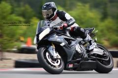 Moto sport BMW S1000RR noire sur le circuit de Mecaglisse Québec