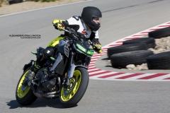 Moto de marque Yamaha FZ09 jaune fluorescent qui prend une courbe à haute vitesse sur le circuit de Mecaglisse Québec