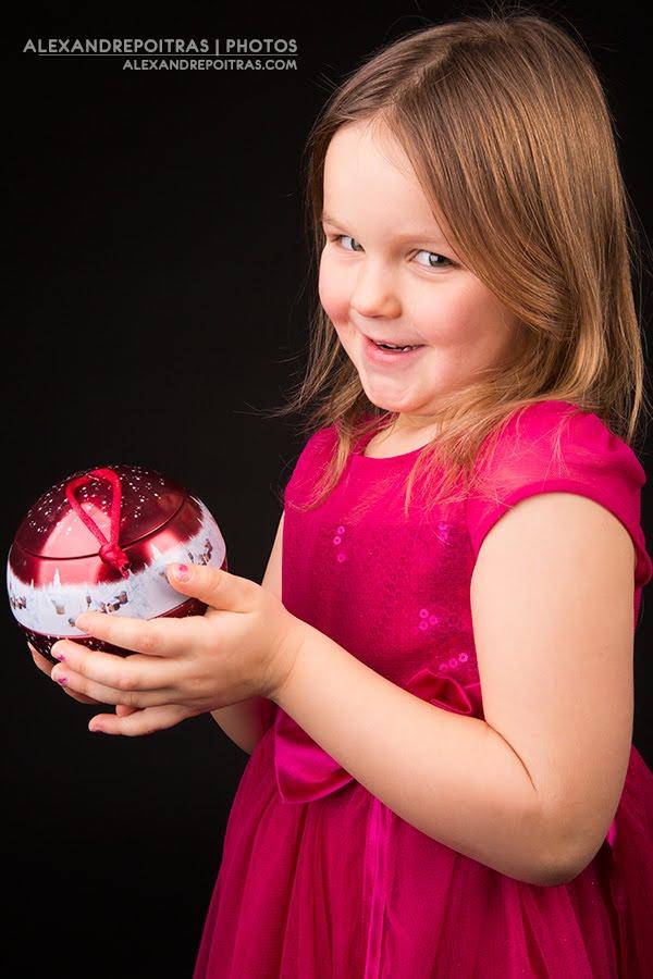 Enfant tenant une boule de Noël rouge dans ses mains